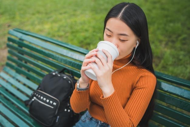 Portrait de jeune femme asiatique, écouter de la musique avec des écouteurs et boire une tasse de café dans le parc à l'extérieur.