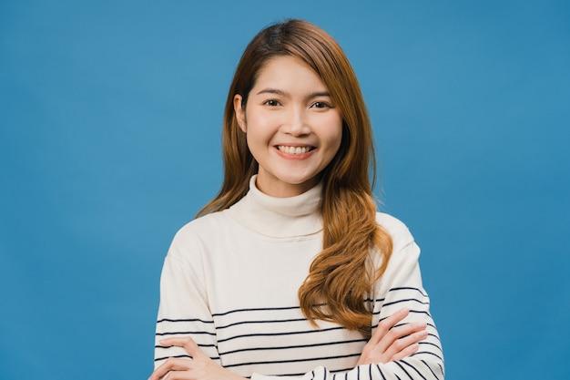 Portrait d'une jeune femme asiatique avec une expression positive, les bras croisés, un large sourire, vêtue de vêtements décontractés et regardant devant le mur bleu