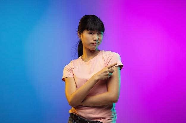 Portrait de jeune femme asiatique sur fond de studio dégradé en néon. beau modèle féminin dans un style décontracté. concept d'émotions humaines, expression faciale, jeunesse, ventes, publicité. prospectus