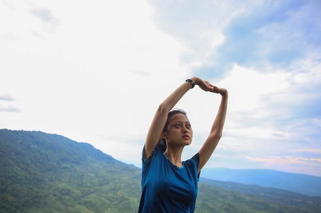 Portrait de jeune femme asiatique en forme et sportive faisant des étirements sur la montagne.
