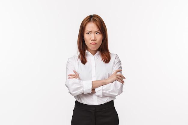 Portrait de jeune femme asiatique grincheuse et offensée, croisez les mains sur la poitrine défensive pose en colère, détournez le regard comme étant insulté et scandalisé par quelqu'un d'être impoli envers elle, mur blanc