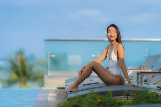 Portrait jeune femme asiatique heureux sourire se détendre autour de la piscine dans l'hôtel resort
