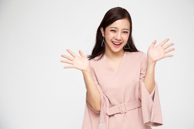 Portrait de jeune femme asiatique hurlant excité debout en robe rose isolé, wow et concept surpris