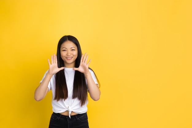 Portrait de jeune femme asiatique isolée sur mur jaune