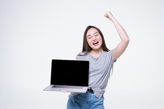 Portrait d'une jeune femme asiatique joyeuse pointant le doigt sur un ordinateur portable à écran blanc isolé sur un mur blanc