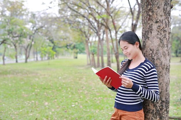 Portrait jeune femme asiatique avec livre debout s'appuyer contre le tronc d'arbre dans le parc en plein air