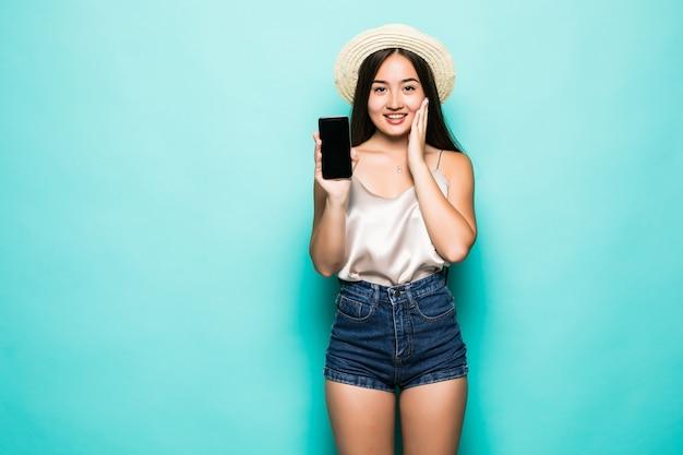 Portrait de jeune femme asiatique montrant son téléphone mobile sreen blanc isolé sur fond vert.