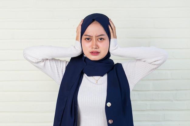 Portrait d'une jeune femme asiatique musulmane portant un hijab et mettant la main et se couvre les oreilles.