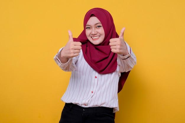 Portrait de jeune femme asiatique portant le hijab donne deux pouces et regarde joyeusement l'expression