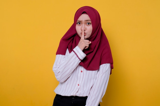 Portrait de jeune femme asiatique portant le hijab montrant l'expression silencieuse s'il vous plaît