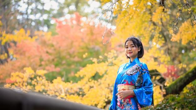 Portrait de jeune femme asiatique portant l'histoire de la mode kimono bleu japonais debout dans le parc à la saison d'automne au japon