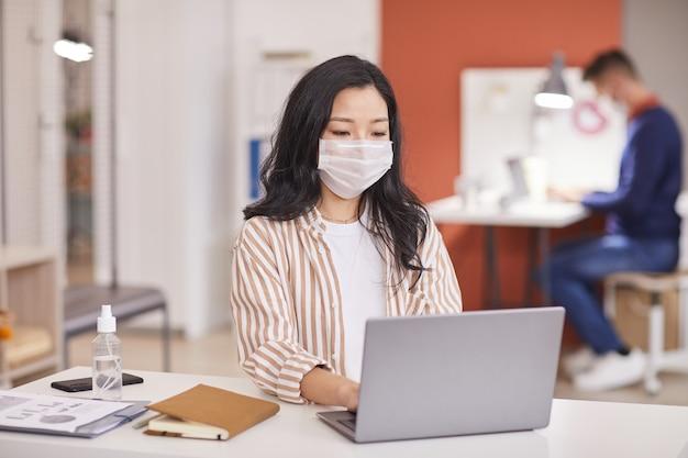 Portrait de jeune femme asiatique portant un masque et à l'aide d'un ordinateur portable tout en travaillant au bureau au bureau avec une bouteille de désinfectant en premier plan, copiez l'espace
