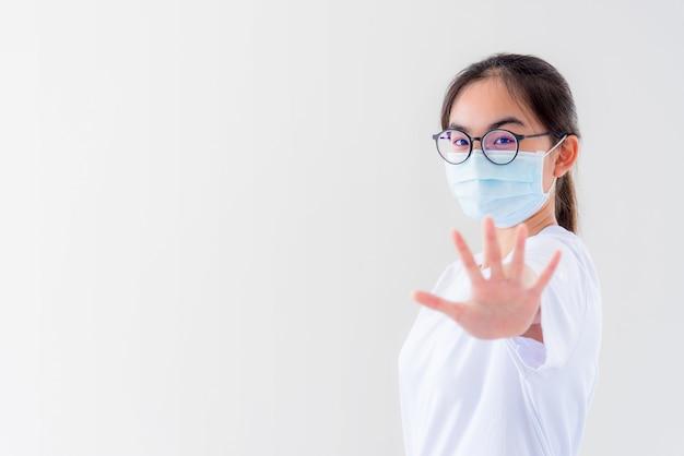 Portrait une jeune femme asiatique porte des lunettes et un masque pour se protéger contre le coronavirus en regardant la caméra, une fille montre les mains arrête l'épidémie de coronavirus isolée sur fond blanc arrête le virus covid 19 concept