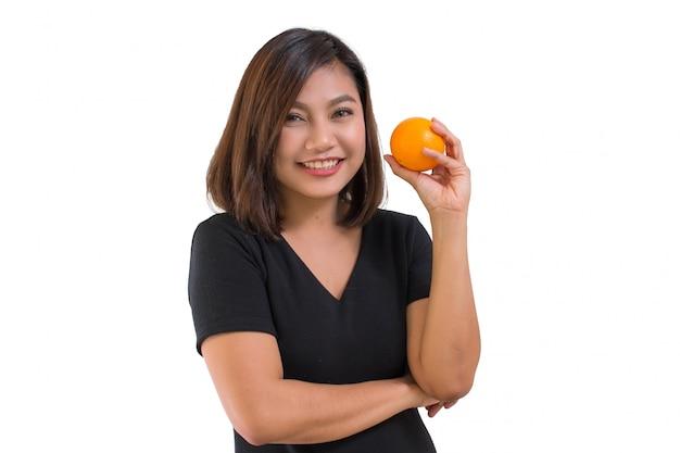 Portrait de jeune femme asiatique porter une chemise noire tenant des fruits orange et sourire.