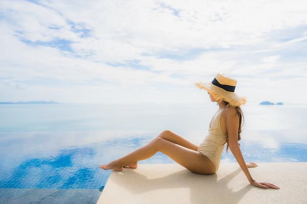 Portrait de jeune femme asiatique se détendre sourire heureux autour de la piscine dans l'hôtel et resort