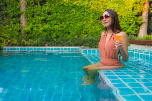 Portrait jeune femme asiatique se détendre sourire heureux autour de la piscine de l'hôtel