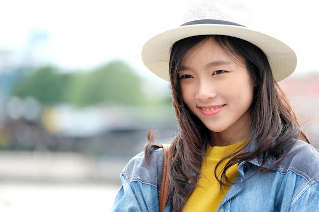 Portrait de jeune femme asiatique souriant avec bonheur au fond de la ville en plein air