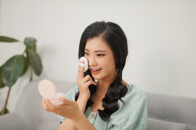 Portrait de jeune femme asiatique souriante appliquant une fondation de coussin sur son visage