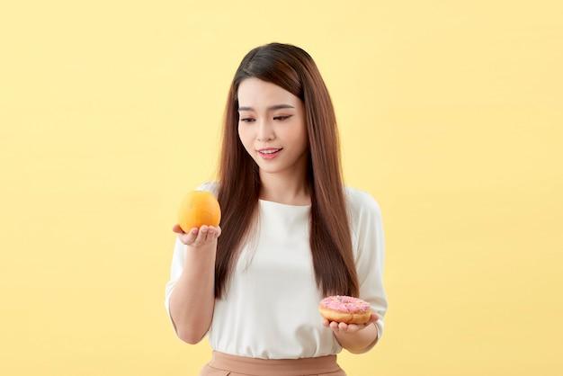 Portrait d'une jeune femme asiatique souriante choisissant entre beignet et orange isolé sur fond jaune
