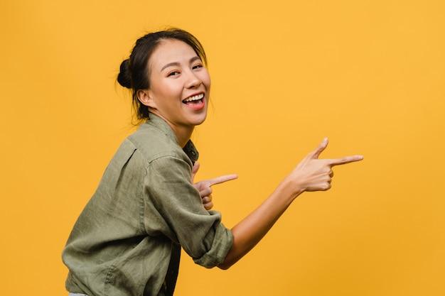 Portrait d'une jeune femme asiatique souriante avec une expression joyeuse, montre quelque chose d'étonnant dans un espace vide dans un tissu décontracté isolé sur un mur jaune. concept d'expression faciale.