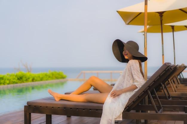 Portrait jeune femme asiatique sourire heureux se détendre autour de la piscine extérieure
