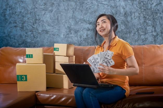 Portrait jeune femme asiatique tenant des lots de billets de 100 dollars américains sont assis sur le canapé de sa chambre