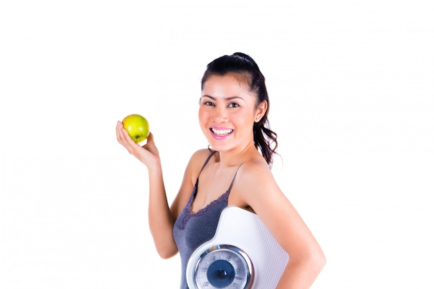 Portrait de jeune femme asiatique tenant la pomme et la balance