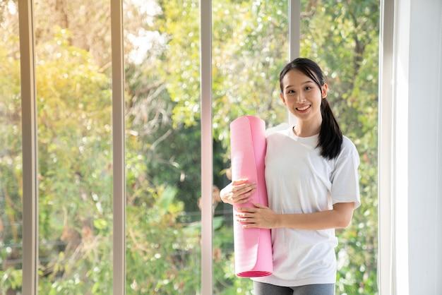 Portrait jeune femme asiatique tenir un tapis de yoga après la classe avec copie espace