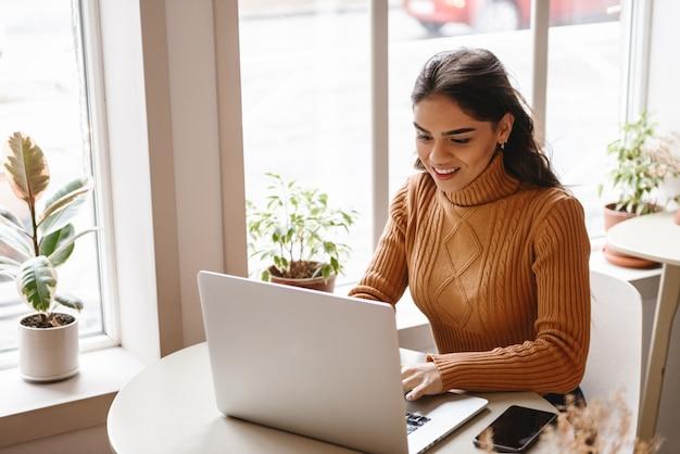 Portrait d'une jeune femme assez belle assise dans un café à l'intérieur à l'aide d'un ordinateur portable.