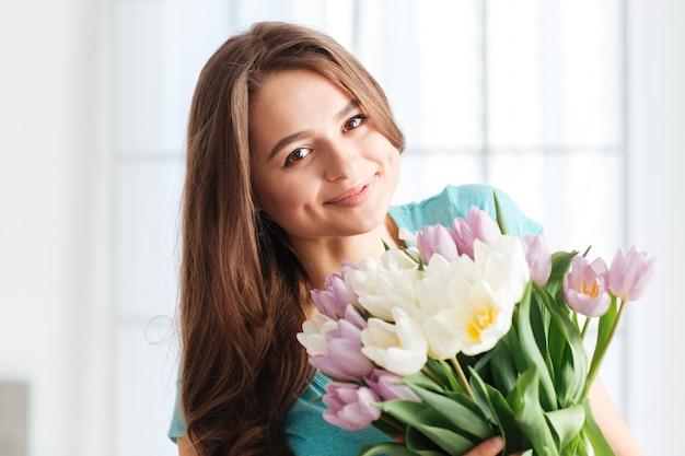 Portrait de jeune femme assez gaie avec le bouquet des fleurs devant la fenêtre