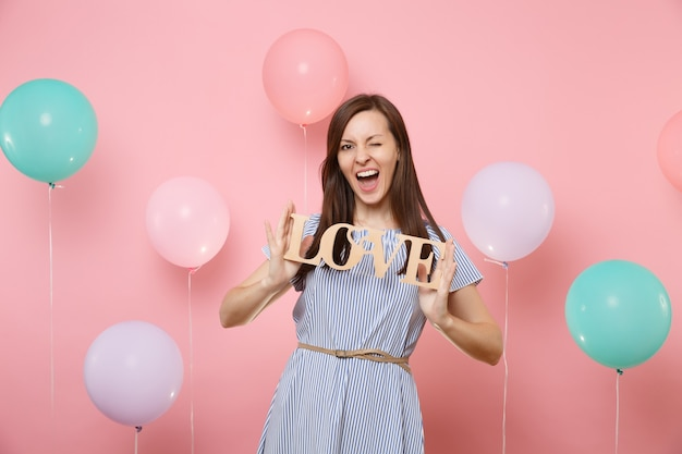 Portrait d'une jeune femme assez heureuse en robe bleue clignotant tenant des lettres de mots en bois amour sur fond rose avec des ballons à air colorés. fête d'anniversaire, concept d'émotions sincères.