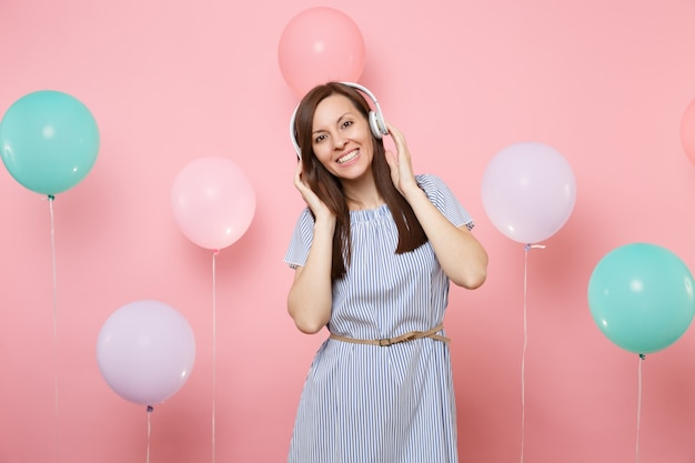 Portrait d'une jeune femme assez joyeuse avec des écouteurs portant une robe bleue écoutant de la musique en gardant les mains près de la tête sur fond rose pastel avec des ballons à air colorés. concept de fête d'anniversaire.