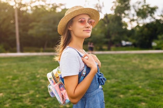 Portrait de jeune femme assez souriante en chapeau de paille et lunettes de soleil roses marchant dans le parc
