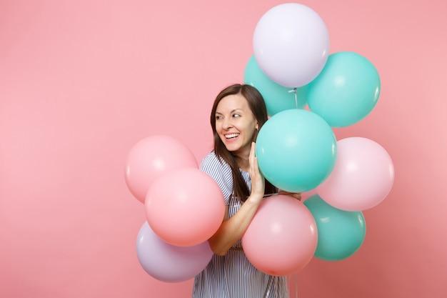Portrait d'une jeune femme assez souriante en robe bleue tenant des ballons à air colorés regarde de côté sur l'espace de copie isolé sur fond rose vif. fête d'anniversaire, concept d'émotions sincères.