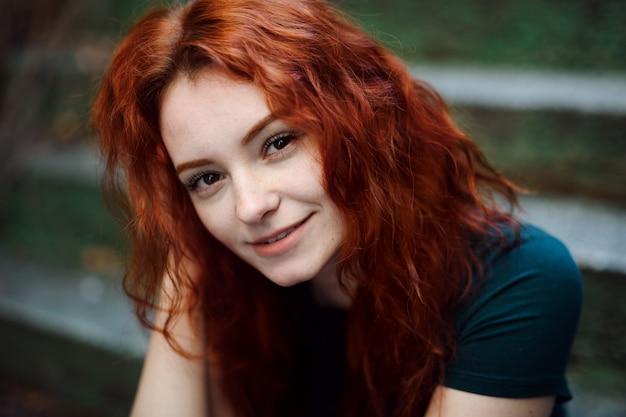 Un portrait de jeune femme assise à l'extérieur sur un escalier en ville, regardant la caméra.