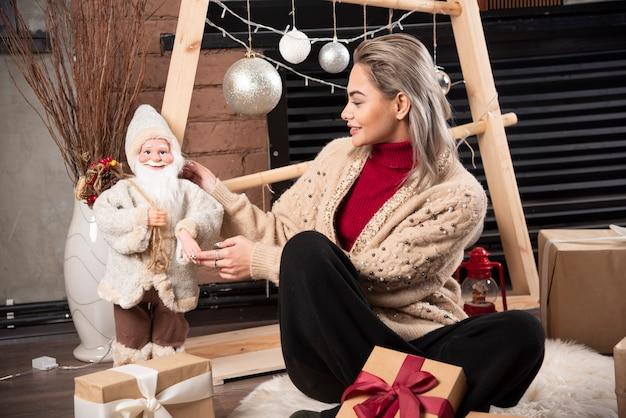 Portrait de jeune femme assise et posant avec un jouet du père noël.photo de haute qualité