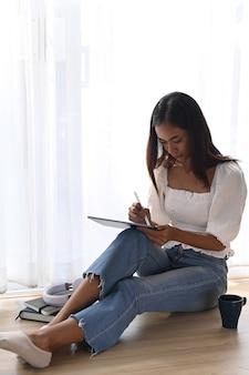 Portrait de jeune femme assise sur le sol dans un salon confortable et utilisant une tablette numérique.