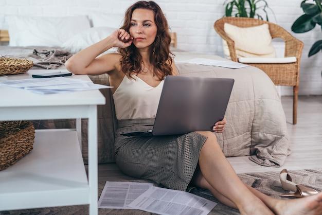 Portrait de jeune femme assise sur le sol avec un ordinateur portable et en détournant les yeux.