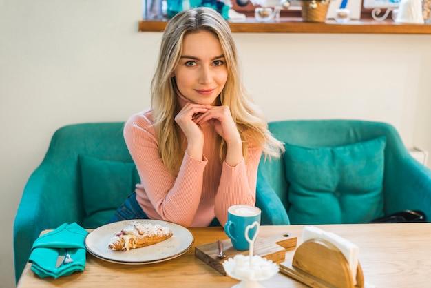 Portrait d'une jeune femme assise à table avec un croissant et une tasse à café