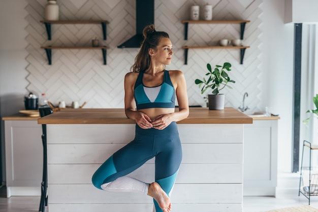 Portrait d'une jeune femme athlétique dans la cuisine.