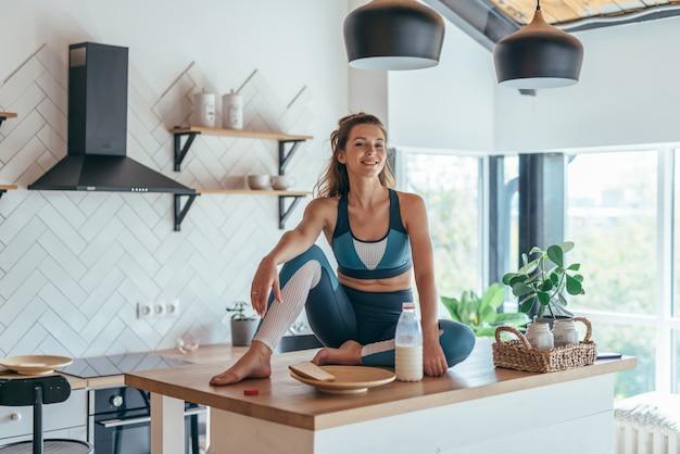 Portrait d'une jeune femme athlétique à la maison dans la cuisine.