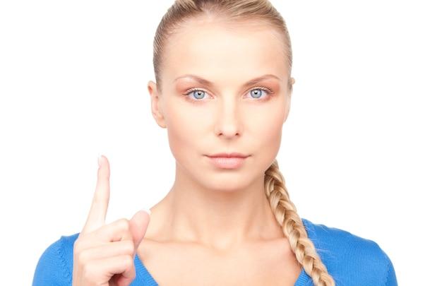 Portrait de jeune femme attirante avec son doigt vers le haut
