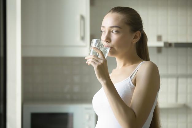Portrait d'une jeune femme attrayante et buvant de l'eau