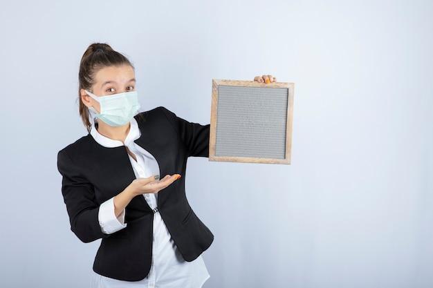 Portrait de jeune femme au masque tenant le cadre sur un mur blanc. photo de haute qualité