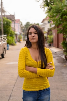 Portrait de jeune femme aux bras croisés dans les rues à l'extérieur