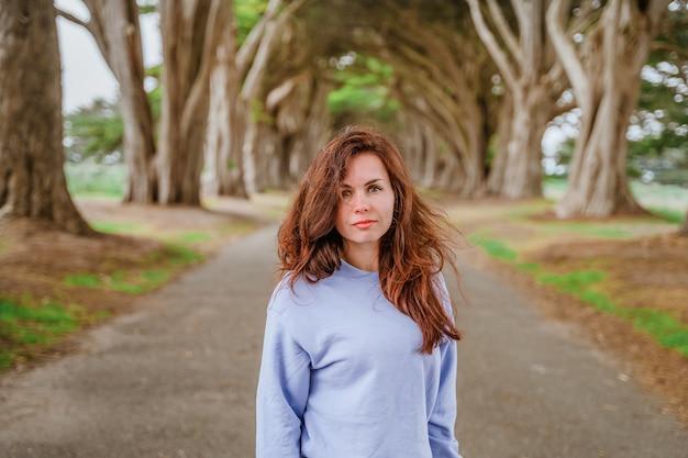 Portrait d'une jeune femme aux cheveux longs dans un tunnel de cyprès