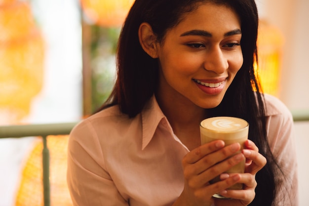 Portrait D'une Jeune Femme Aux Cheveux Noirs Heureuse Se Sentant Bien Et Souriante Tout En Ayant Un Verre De Latte Dans Ses Mains Photo Premium