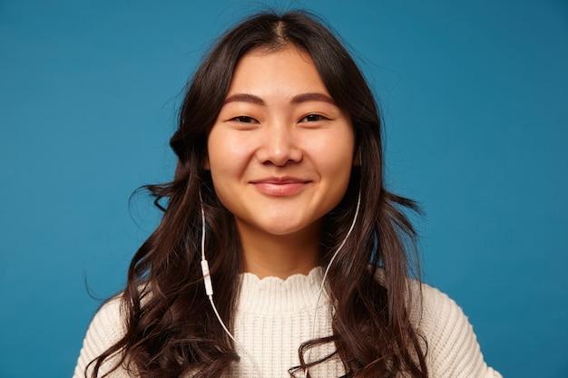 Portrait de jeune femme aux cheveux noirs séduisante heureuse avec des écouteurs