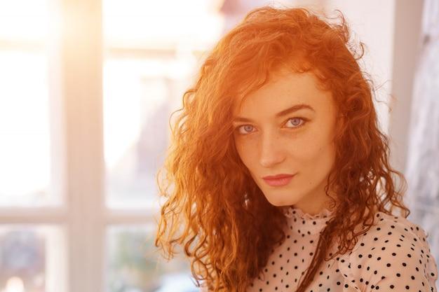 Portrait d'une jeune femme aux cheveux rouges sur la fenêtre