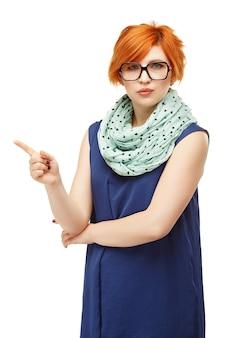 Portrait d'une jeune femme aux cheveux roux avec une expression sévère sur son visage et un index surélevé